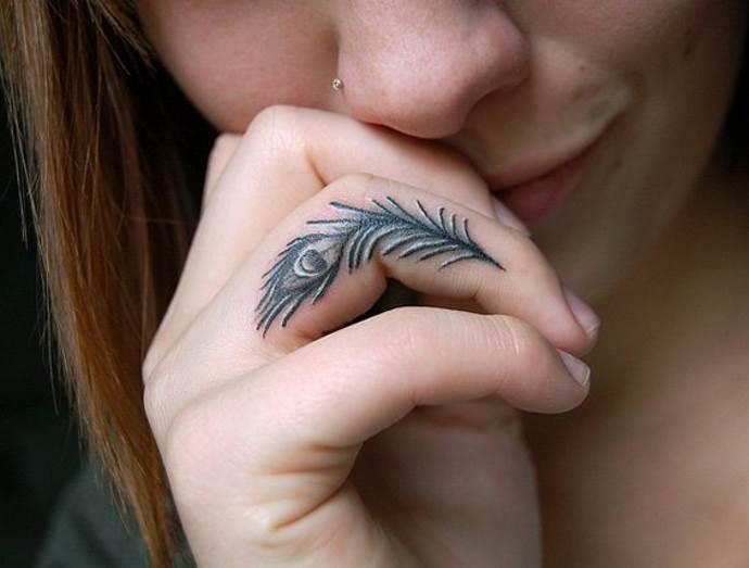 перо павлина на пальце у девушки